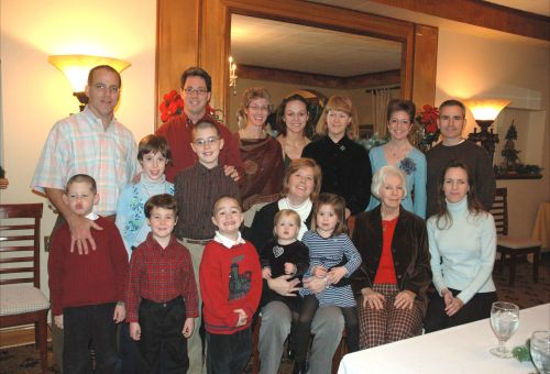 Mark (L) in a Christmas photo a few years ago. Liz is seated, center, holding their two daughters. TOC in black velvet shirt.