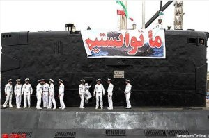 """Iranian navy officers celebrate national defense on Yunes' sister boat, Tareq (under a sign reading -- what else -- """"Yes, we can!"""")"""