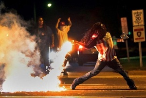 Protester in Ferguson tosses a flash grenade back at police, 13 August. (Twitter image)